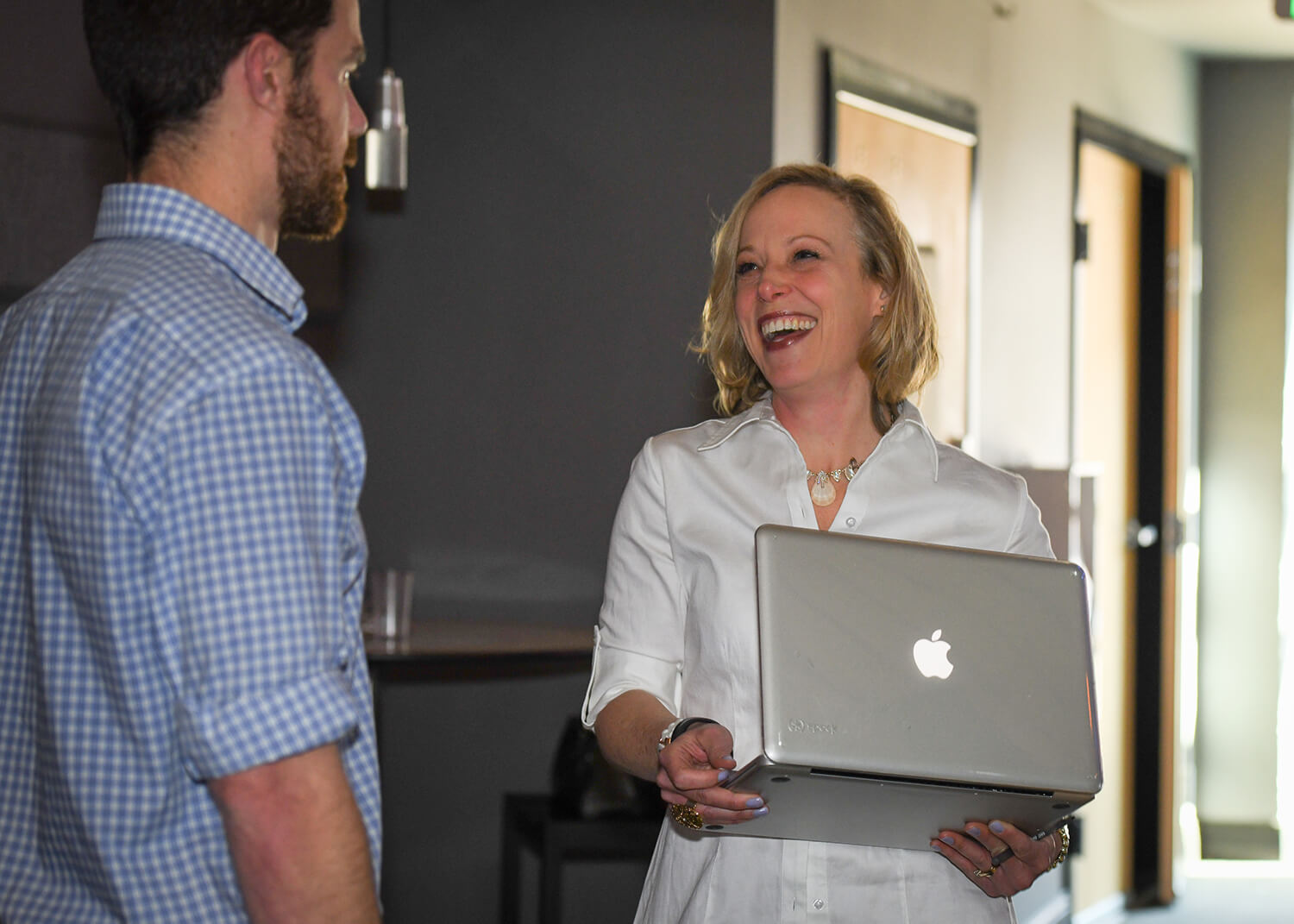 Cindy laughing holding laptop with client